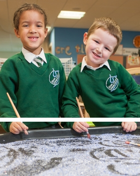 Pupils at River View Primary School writing in sand