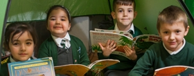 Pupils reading books in a tent at River View Primary School