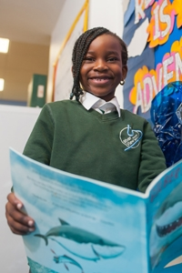 A pupil reading a book at River View Primary School