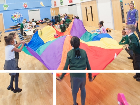 Pupils playing with a parachute in the school hall at River View Primary School