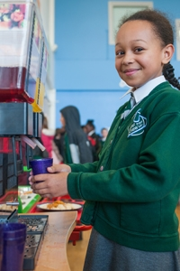 A pupil getting juice from The River View Cafe in River View Primary School