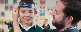 A pupil and a teacher in a lesson at River View Primary School working with a tape measure