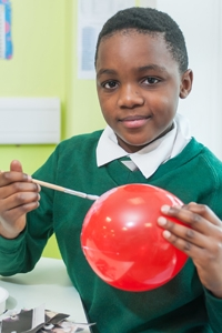 A pupil making paper mache in a lesson at River View Primary School